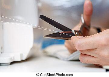 Woman cuts thread with scissors