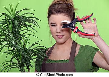 woman cutting a plant