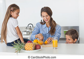 Woman cutting an orange for her children