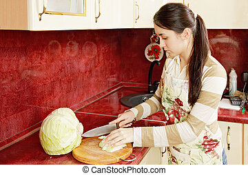 Woman cutting cabbage - Young woman cutting cabbage in...