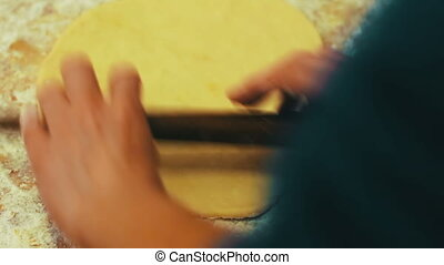 Woman cutting dough with a knife