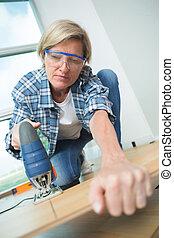 Woman cutting floorboard with jigsaw
