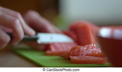 Woman cutting fresh salmon fillet in kitchen, close up view.