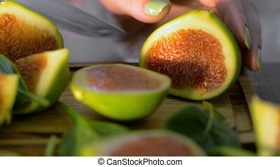Woman cutting green appetizing figs - Close-up shot of woman...