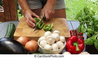 Woman cutting green pepper on a wooden board