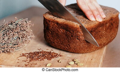 Woman cutting homemade bread with knife on wooden board, 4k