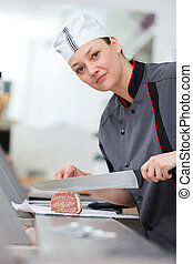 woman cutting meat