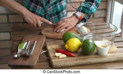 Woman cutting onion for guacamole recipe in kitchen.