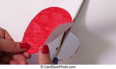 Woman cutting out red heart shape