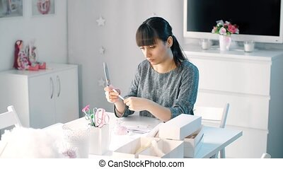 Woman cutting paper using scissors while sitting at table