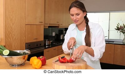 Woman cutting peppers in the kitchen