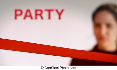 Woman cutting red ribbon at a party