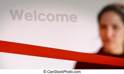 Woman cutting red ribbon with welcome sign