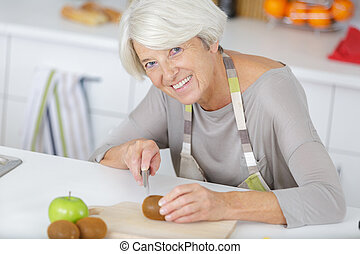 woman cutting tomato on wooden board