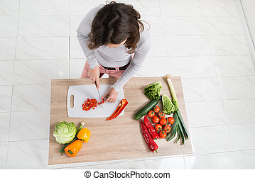 Woman Cutting Vegetable In Kitchen
