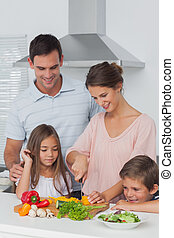 Woman cutting vegetables next to her children