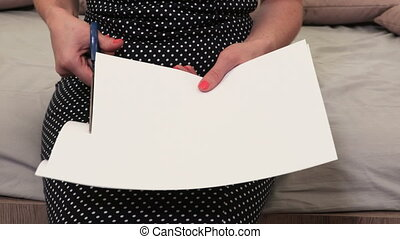 Woman cutting white paper blank