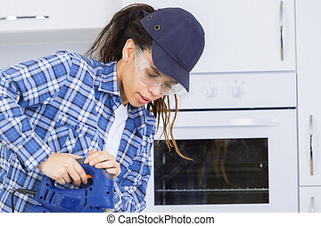 woman cutting wood while fitting a kitchen