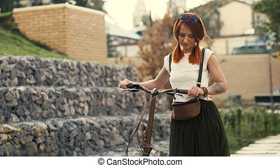 Woman cyclist and bicycle. Woman bike city. Red hair girl...