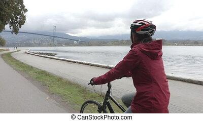 Woman Cyclist biking in Stanley Park by Lions Gate Bridge on...
