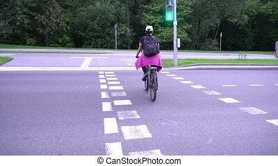 Woman cyclist, female riding bicycle on street crossing...