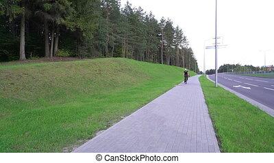 Woman cyclist, female riding bicycle on street, speeding...