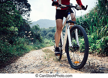 woman cyclist legs riding mountain bike on trail in forest