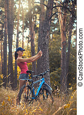 woman cyclist makes selfie in the park.