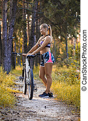 Cyclist resting under a tree and drinking water