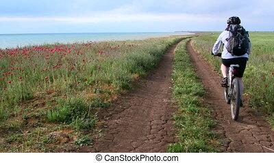 Woman cyclist rides bike along the seashore down a dirt road