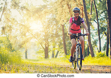 woman cyclist rides in the forest on a mountain bike. -...