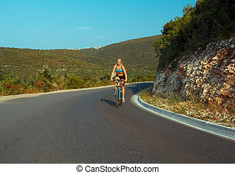 Woman cyclist riding a bike on a mountain road