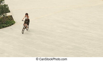 Woman cyclist riding a bike on paved road at square on summer day