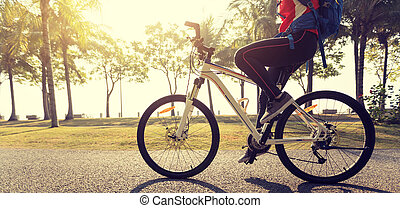 woman cyclist riding bike in a tropical park