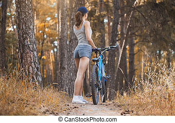 woman cyclist riding mountain bike in the forest