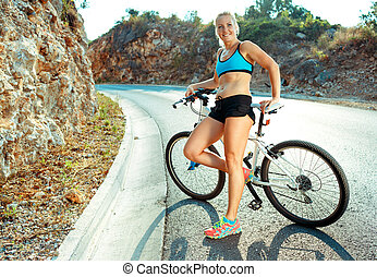 Woman cyclist standing near a bike on a mountain road