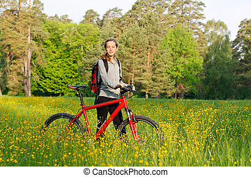 Woman cyclist with bike and backpack among the blooming nature