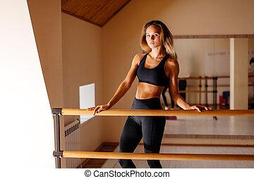 woman dancer posing near barre in ballet studio