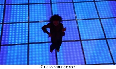 Woman dances at dark discotheque with illuminated floor