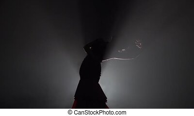 Woman dances flowing movements with hands. Light from behind. Smoke background. Slow motion. Silhouette