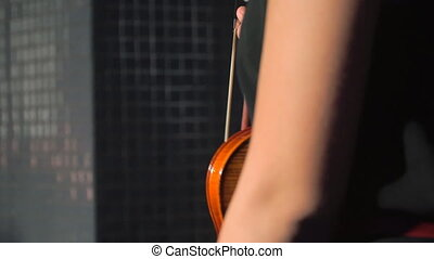 Woman dances while holding a violin - A young woman dances...