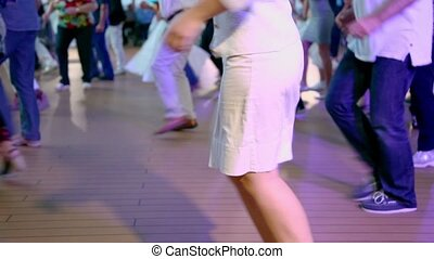Woman dances with many other people in latin american style