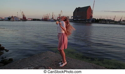 woman dancing and drink coffee at sunset river port