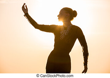 Woman dancing at sunrise