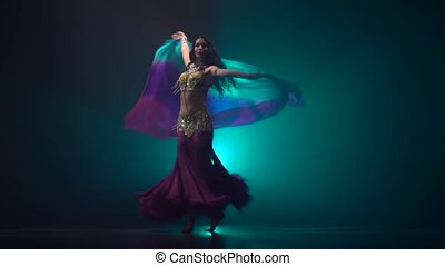 Woman dancing belly dance in dark studio. Smoke background....