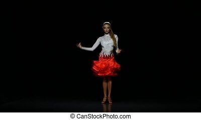 Woman dancing cha-cha-cha in a studio on a dark background