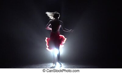 Pretty lady dancing rumba, samba, cha-cha-cha, latin dance in the studio, silhouette, rear light lamp, red - white dress with sequins, long hair, long legs, slow motion
