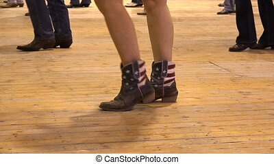 Woman dancing cowboy line dance at a folk country event, USA...