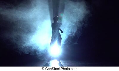 Woman dancing elements of sport - ballroom dance in the studio, silhouette. Slow motion