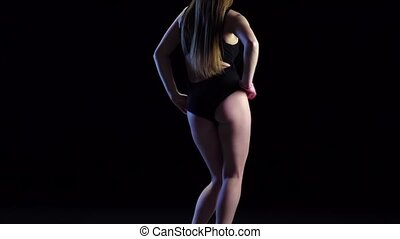 Woman dancing her buttocks. Black background in slow motion